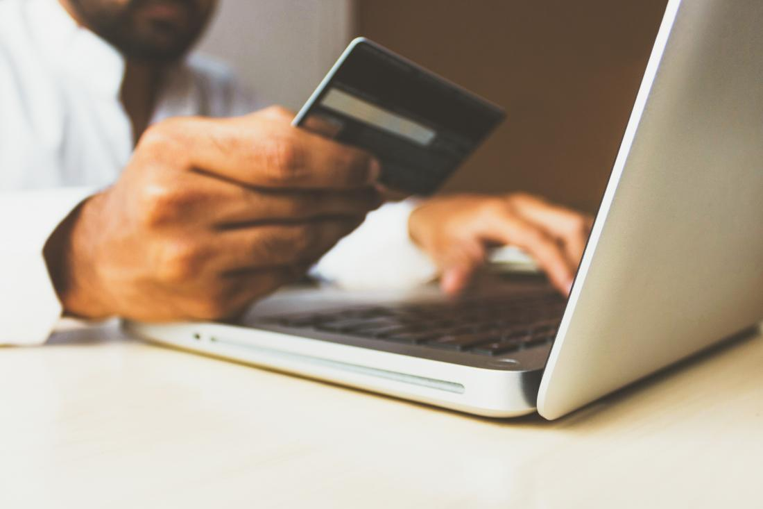 Credit card held in front of laptop screen